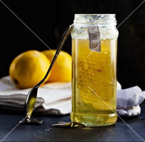 A honeycomb in a jar of honey with lemons in the background