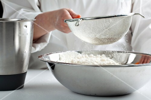 Flour being sifted into a large mixing bowl