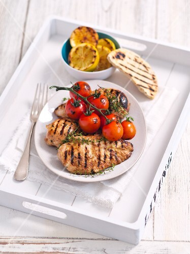 Grilled chicken breast with lemons and tomatoes