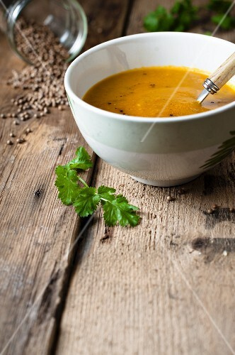 Carrot and coriander soup on a rustic wooden surface