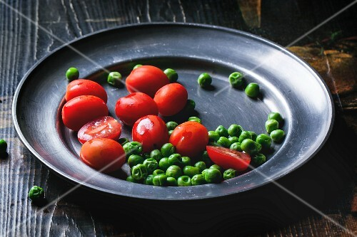 Cherry tomatoes and peas on a metal plate