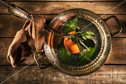 A freshly picked orange in a copper saucepan