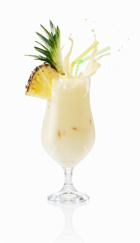 A pina colada splashing out of the glass