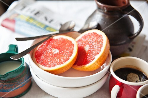 Breakfast with coffee, grapefruit and newspapers