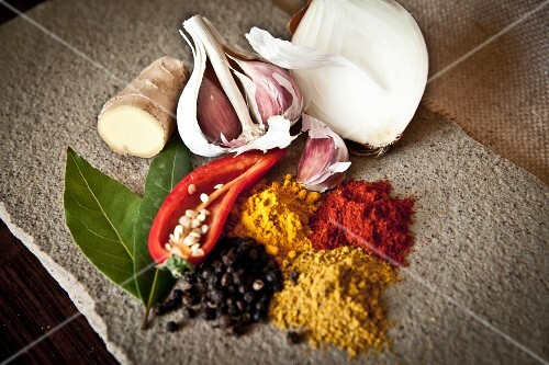 A selection of Indian spices, garlic, onion and chilli peppers
