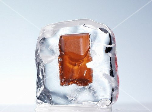 A piece of chocolate in an ice cube