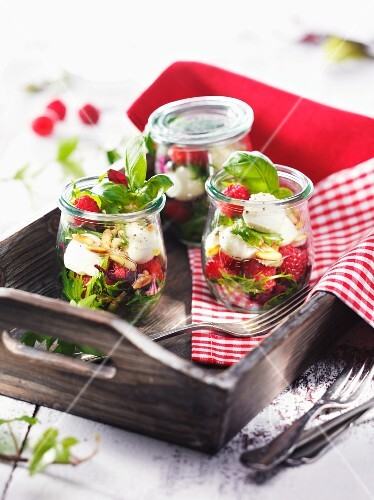 Jars of raspberries with mozzarella and basil on a wooden tray