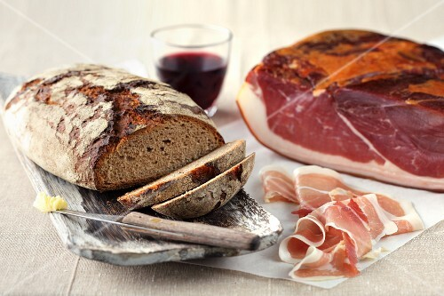 A loaf of sliced bread, ham, a knife with butter and a glass of red wine