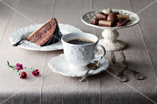 A cup of coffee with a slice of cake and various pralines
