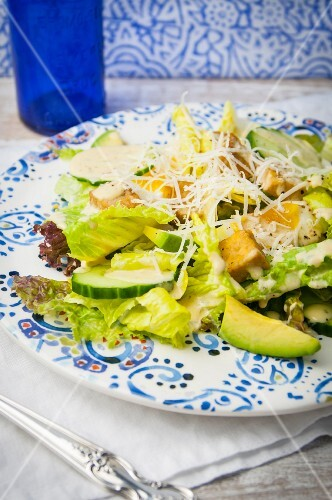 A Caesar salad with avocado, tempeh and Parmesan cheese