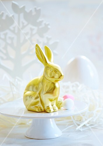A golden Easter bunny on a cake stand