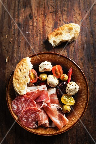 An antipasti platter featuring proscuitto, mozzarella, tomatoes, olives, salami and bread (Italy)