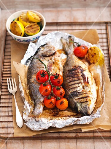 Grilled fish with tomatoes and lemons in aluminium foil on a grill rack