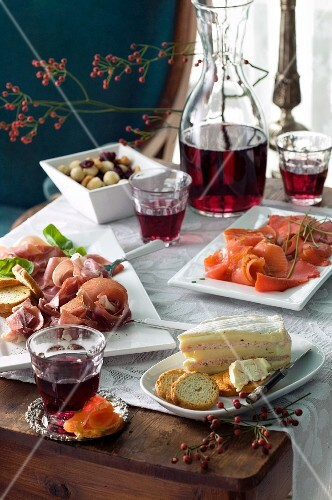 A buffet with salmon, cheese, ham, olives and red wine