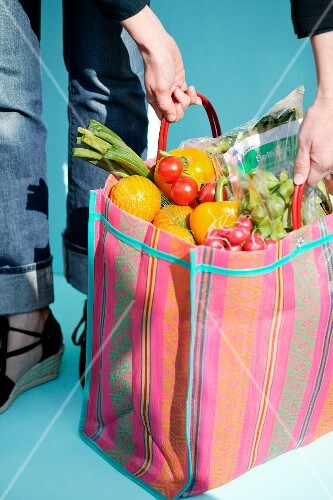 A woman holding a shopping bag of fresh fruit and vegetables