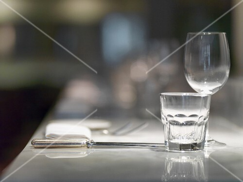 A place setting in a restaurant with glasses, cutlery and a napkin