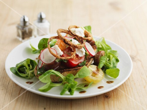Lamb's lettuce with goat's cheese, radishes, tomatoes and onion rings on toasted bread