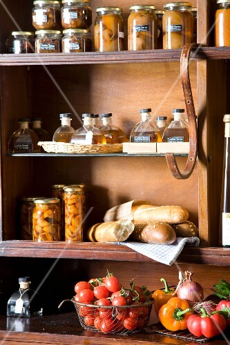 Jars, bread and fresh vegetables in a pantry