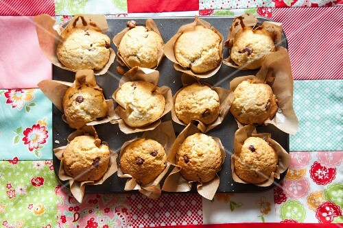 Freshly baked choc-chip muffins on a baking tray
