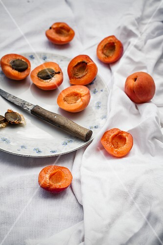 Halved apricots on a plate and next to it