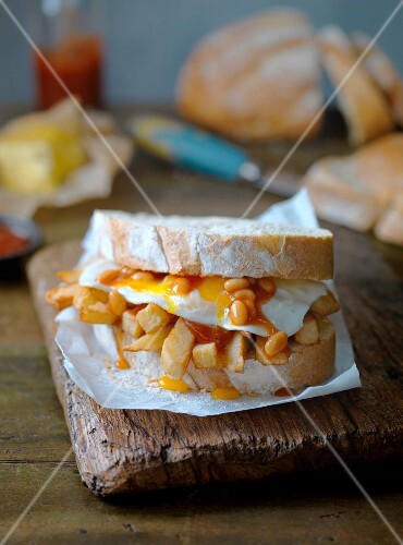 A fried egg, baked beans and chip sandwich