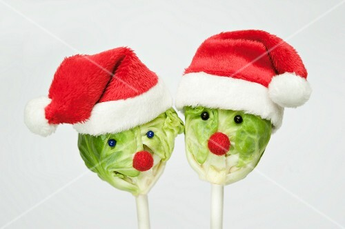 Two Brussels sprouts on sticks with Christmas hats and faces