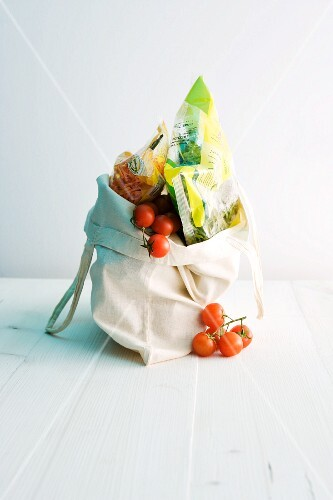 Cherry tomatoes and wrapped food in a shopping bag