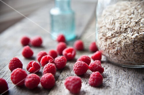 Fresh raspberries and a jar of oats on wooden table