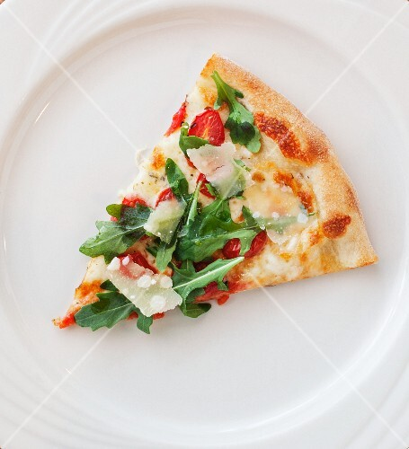 A slice of pizza with tomatoes, cheese and rocket