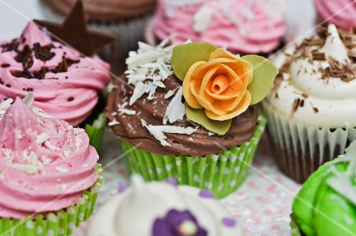Various cupcakes with sugar flowers, chocolate stars and grated chocolate