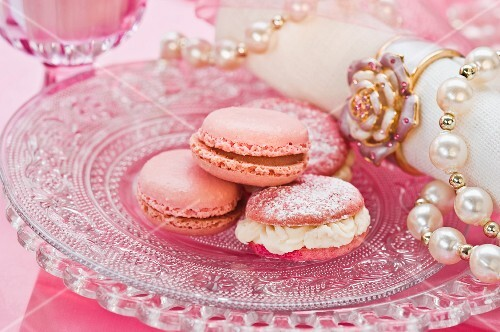 Pink macaroons on a glass plate with a pearl necklace and a napkin
