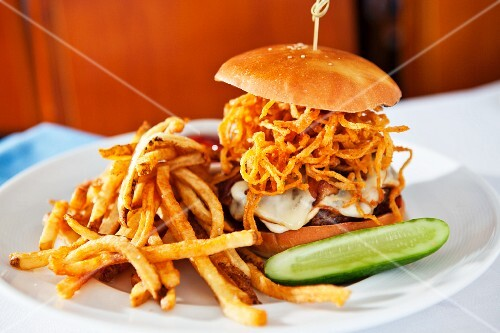 A cheeseburger with fried onions and chips