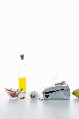 An arrangement featuring a vacuum packaging machine, a bottle of oil and chilli peppers