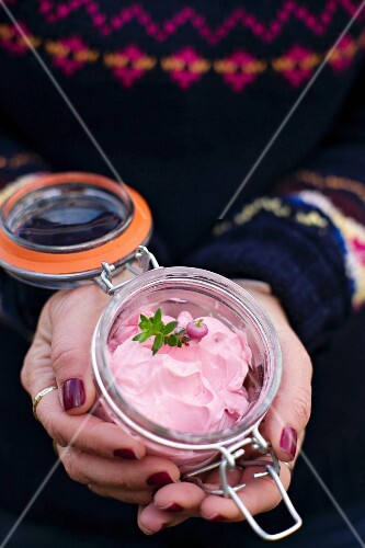 A woman holding a jar of beetroot cream cheese