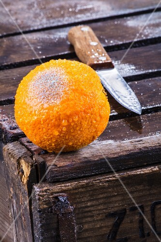 A mouldy orange with a knife on a wooden crate