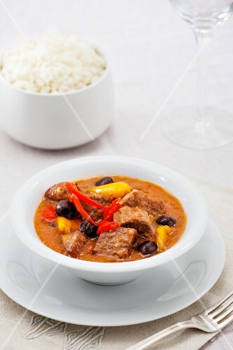 Beef stew with peppers, black olives and a side of rice