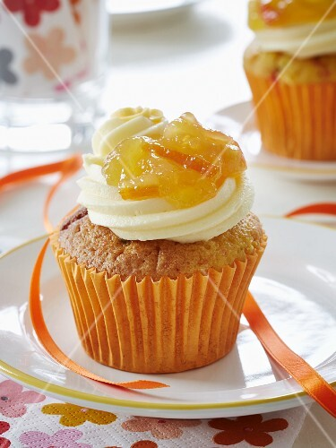 A cupcake with a cream cheese topping and marmalade