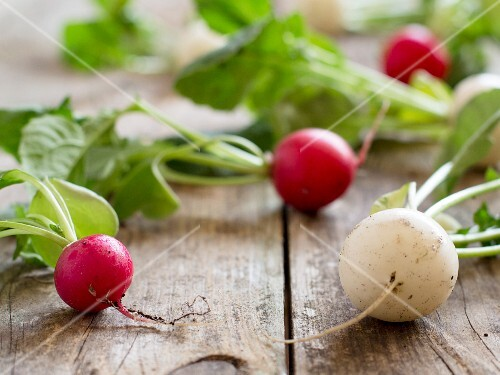 Red and white radishes on a wooden table