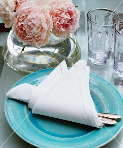 A vase of roses and a place setting with cutlery wrapped in a napkin on a table