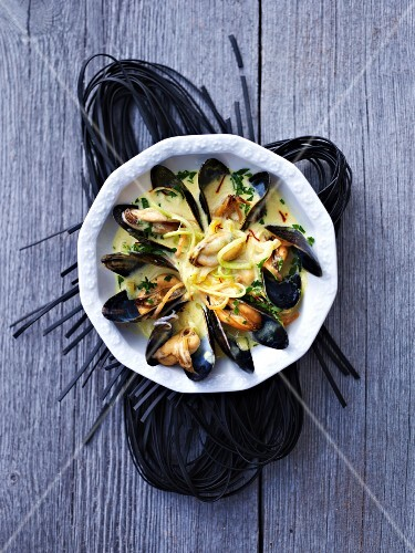 Mussels in a creamy sauce on squid spaghetti