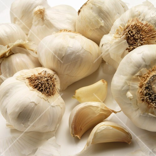 Whole garlic bulbs and three cloves of garlic