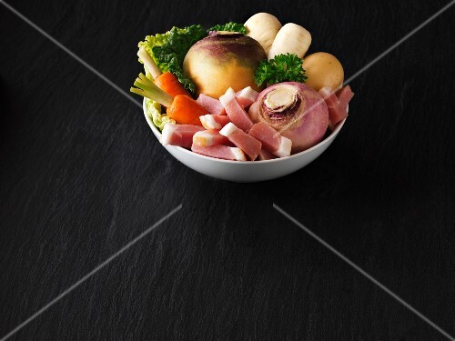 A bowl of fresh vegetables with bacon