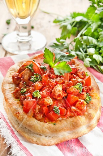 Mini puff pastry pizzas topped with tomatoes, veal and herbs