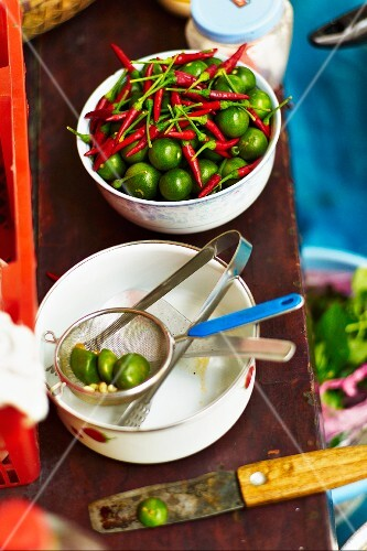 Vietnamese limes and red chillis on a market stand