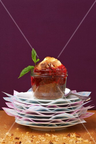 A pecan nut muffin with raspberry jam in a glass jar