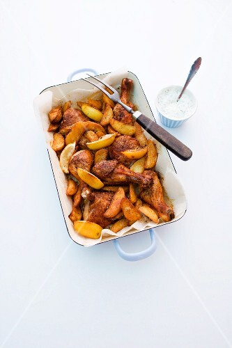Roast chicken with potato wedges and lemons