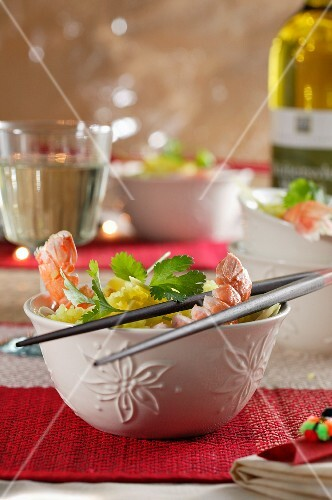 Saffron rice with prawns in a bowl with chopsticks