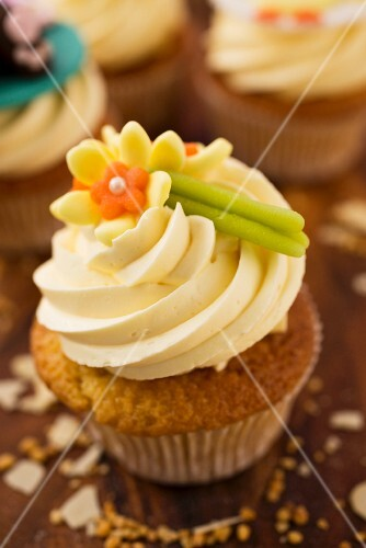 A cupcake decorated with a marzipan flower