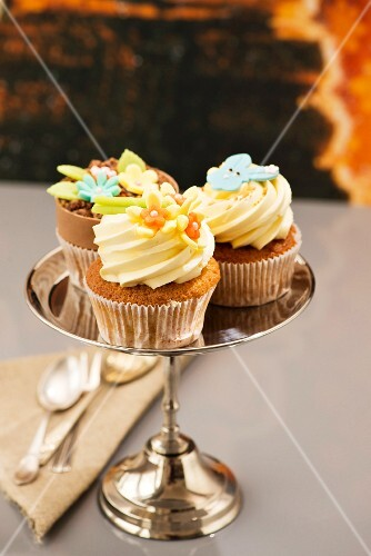 Various Easter cupcakes on a silver cake stand