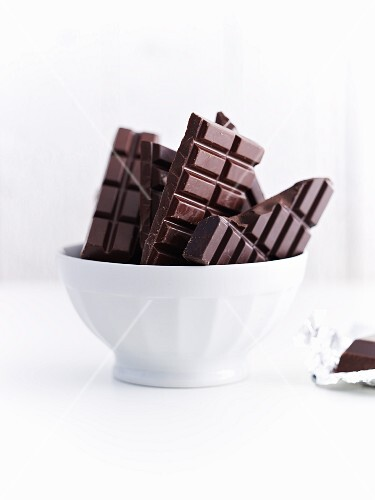 Bars of chocolate in a white ceramic bowl